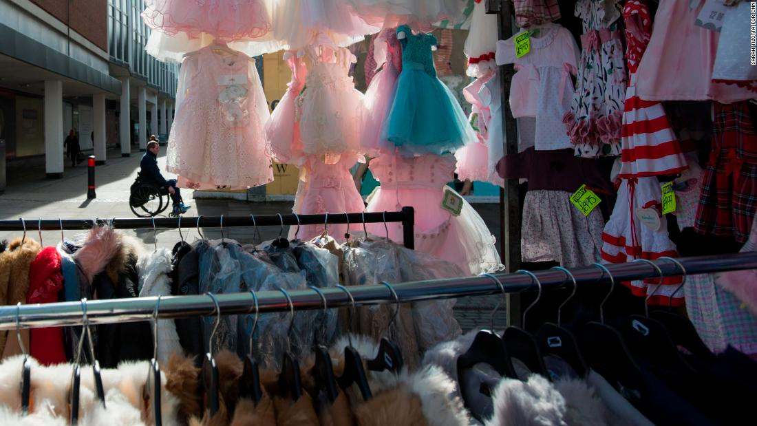 Children's ruffled dresses hang from a stall in Romford Market.