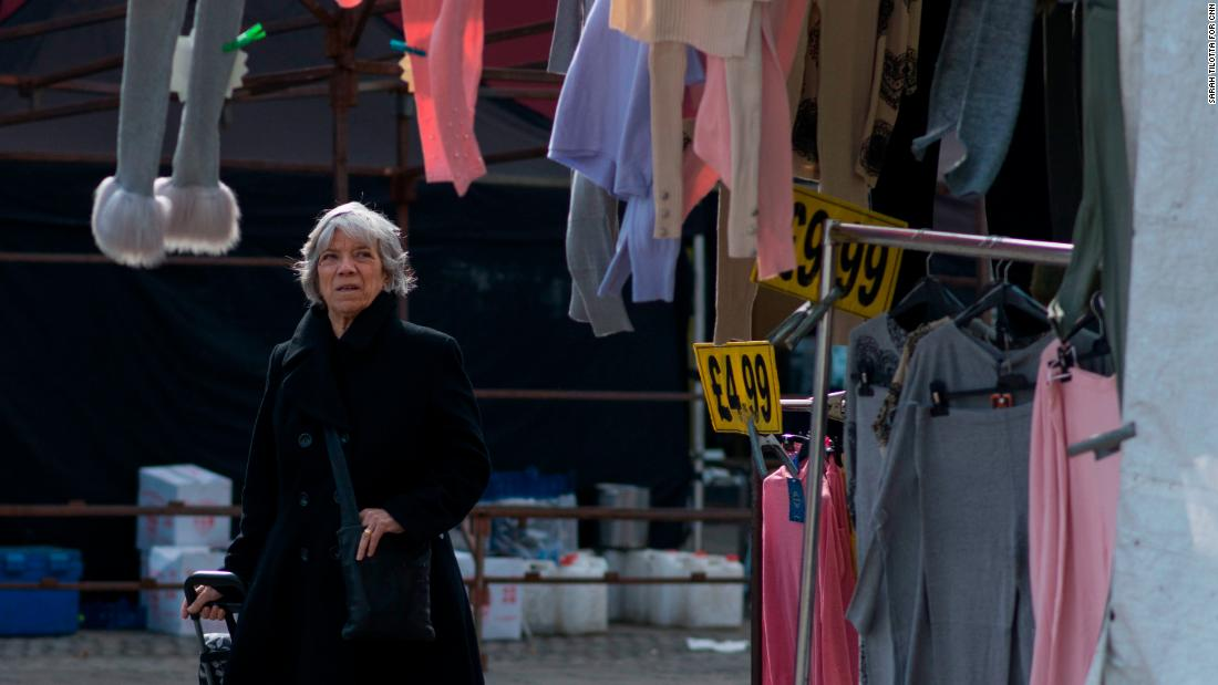 A woman browses through clothes at a market stall.