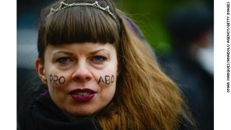 "A woman with ""Pro Abo"" face paint attends a protest against a proposed  law to tighten abortion in Warsaw."