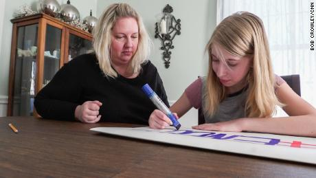 Lauren Milgram makes a sign to take to March for Our Lives with her mother, Erin