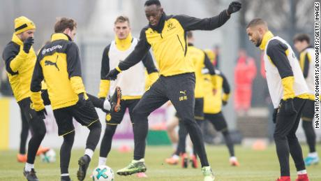 DORTMUND, GERMANY - MARCH 23: Usain Bolt warms up with Mario Gotze #10 of Borussia Dortmund (2L) and players during a training of Borussia Dortmund on March 23, 2018 in Dortmund, Germany. (Photo by Maja Hitij/Bongarts/Getty Images)