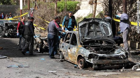 Investigators look over a vehicle destroyed in the Alexandria bombing.