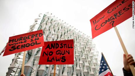 "Protesters hold up signs outside the US Embassy in London, Saturday March 24, 2018,  in solidarity with the ""March for Our Lives"" protest against gun violence. (Stefan Rousseau/PA via AP)"