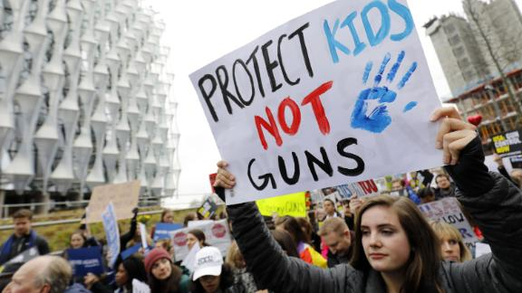 Protestors carry placards and shout slogans during a demonstration calling for greater gun control, outside the US Embassy in south London on March 24, 2018.  The London rally, in solidarity with the US movement