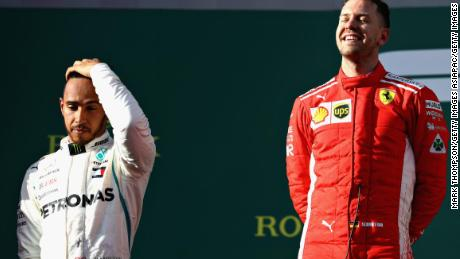 Every picture tells a story.  Sebastian Vettel celebrates on the podium as  second-placed Lewis Hamilton shows his feelings.