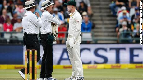 Australian fielder Cameron Bancroft (R) is questioned by Umpires Richard Illingworth (L) and Nigel Llong (C) during the third day of the third Test cricket match between South Africa and Australia at Newlands cricket ground on March 24, 2018 in Cape Town. / AFP PHOTO / GIANLUIGI GUERCIA        (Photo credit should read GIANLUIGI GUERCIA/AFP/Getty Images)