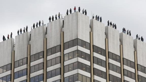 These statues atop a London building represent the 84 men who commit suicide every week in the UK.