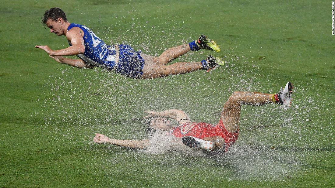 Gold Coast's Lachie Weller, bottom, is tackled by North Melbourne's Kayne Turner during an Australian Football League match on Saturday, March 24.