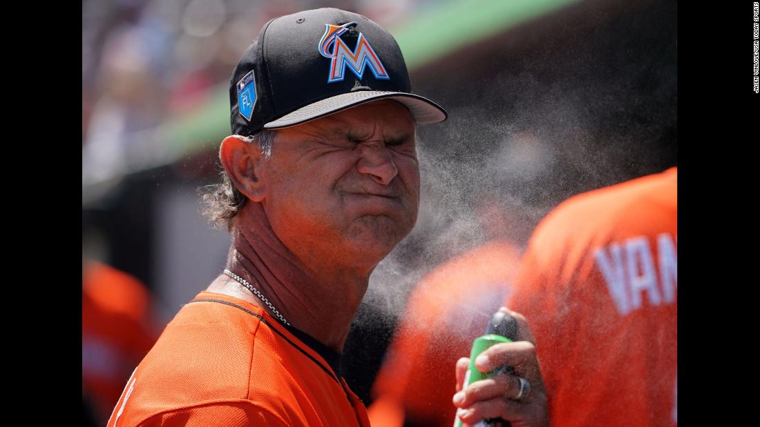 Miami manager Don Mattingly sprays sunscreen on his face before a spring-training game in Jupiter, Florida, on Wednesday, March 21.