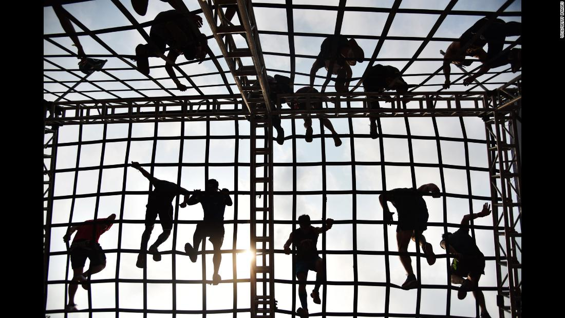 Competitors climb an obstacle during a Spartan Race in Shenzhen, China, on Saturday, March 24.