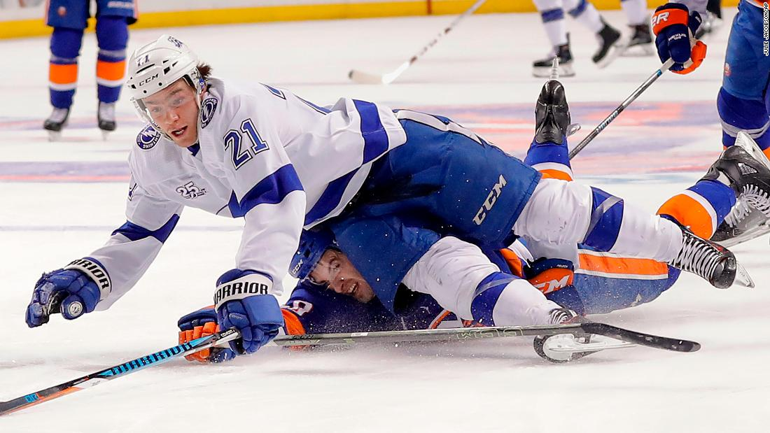 Tampa Bay's Brayden Point, top, is tripped by New York Islanders defenseman Adam Pelech during an NHL game in New York on Thursday, March 22.