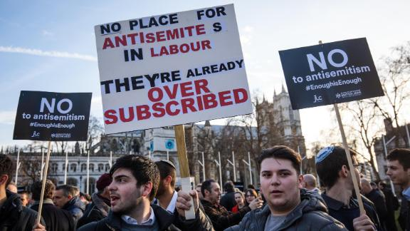 """LONDON, ENGLAND - MARCH 26: Protesters hold placards as they demonstrate in Parliament Square against anti-Semitism in the Labour Party on March 26, 2018 in London, England. The Board of Deputies of British Jews and the Jewish Leadership Council have drawn up a letter accusing Labour Leader Jeremy Corbyn of failing to address anti-Semitism in his party. Mr Corbyn has today apologised to Jewish groups for """"pockets of anti-Semitism"""" in Labour. (Photo by Jack Taylor/Getty Images)"""