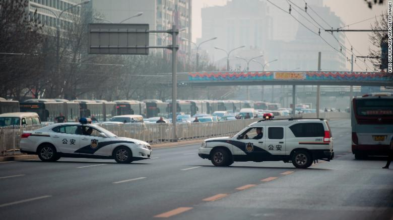 Chinese police cars block a road near the Diaoyutai State Guesthouse in Beijing Tuesday.