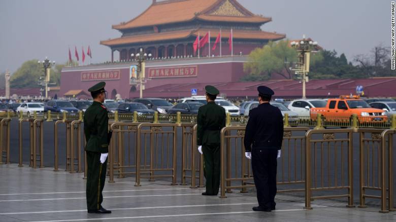 A police (right) and two paramilitary police officers take position near Tiananmen Square in Beijing on Tuesday