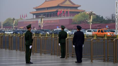 A police and two paramilitary police officers take position near Tiananmen Square on Tuesday.