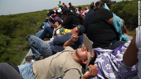 "Central American immigrants ride on top of a freight train near Juchitlan, Mexico, in August 2013. Thousands ride the trains — known as ""la bestia"" (the beast) — during their long journey north to reach the US border."
