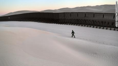 A US Border Patrol agent walks along the US-Mexico border near Felicity, California, in November 2016.