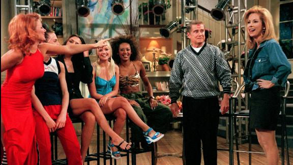"""Kathie Lee Gifford, right, smiles as Geri """"Ginger Spice"""" Halliwell, far left, points to the kiss she planted on Regis Philbin during an appearance by the Spice Girls on """"Live with Regis and Kathie Lee"""" on May 16, 1997."""