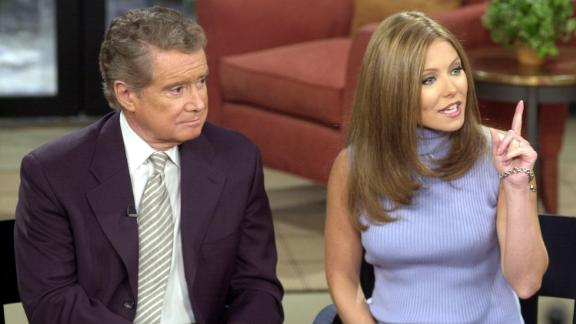 """Talk show host Regis Philbin and new co-host Kelly Ripa speak to the audience during a broadcast of """"Live with Regis and Kelly"""" in New York City on February 5, 2001."""