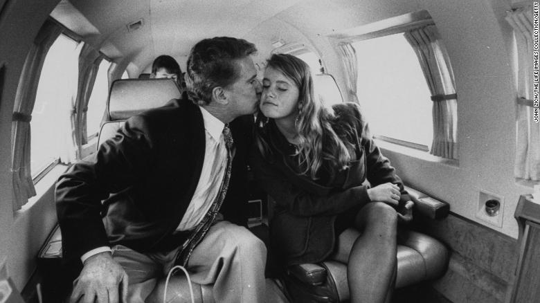 Regis Philbin gives his daughter J.J. a kiss on an airplane en route to Notre Dame University.