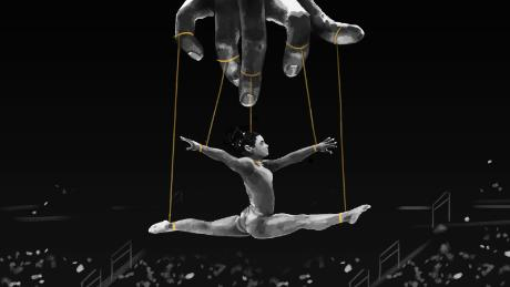 An illustration shows a gymnast hanging in midair. Her arms and legs are in a split position, tied by strings to fingers on a controlling hand above. The image is like that of a puppeteer and his puppet.