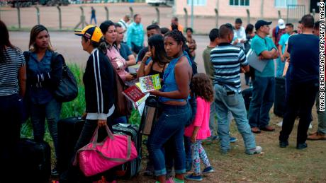 Venezuelans wait in a queue in front of the Brazil Federal Police Office in the Venezuela-Brazil border, at Pacaraima, Roraima, Brazil, on February 28, 2018.   According to local authorities, around one thousand refugees are crossing the Brazilian border each day from Venezuela. With the constant influx of Venezuelan immigrants, most are living in shelters and the streets of Boa Vista and Pacaraima cities, looking for work, medical care and food. Most are legalizing their status to stay and live in Brazil.  / AFP PHOTO / Mauro Pimentel / TO GO WITH AFP STORY by Paula RAMÓN        (Photo credit should read MAURO PIMENTEL/AFP/Getty Images)