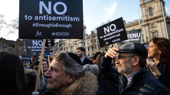 Protesters hold placards as they demonstrate in Parliament Square against anti-Semitism on March 26, 2018 in London.