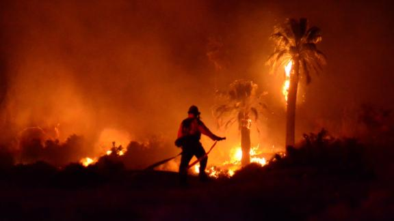 In this Monday, March 26, 2018 photo provided by Steve Raines, a firefighter works at the scene of a fire that broke out at Joshua Tree National Park, damaging a historical landmark. The National Park Service said the fire that broke out late Monday damaged the Oasis of Mara, a site settled by Native Americans who planted the 29 palm trees that inspired the name of the city of Twentynine Palms. (Steve Raines Photography via AP)