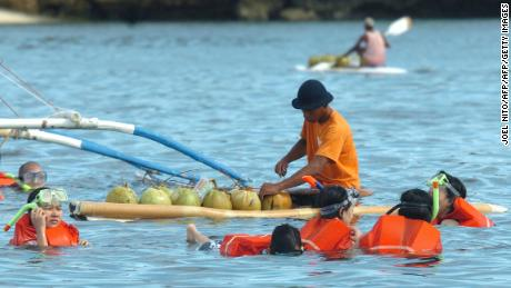 A man on a surfboard sells fresh coconut juice to people swimming in the waters off the central Philippine resort island in this shot dated 2005.