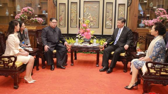 In this March 27, 2018, photo, North Korean leader Kim Jong Un, center left, and his wife Ri Sol Ju, left, talk with Chinese counterpart Xi Jinping, second from right, and his wife Peng Liyuan at Diaoyutai State Guesthouse in Beijing. North Korea