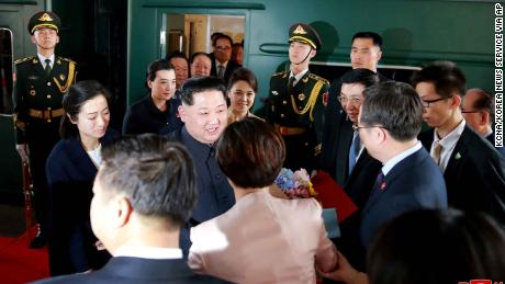"In this March 26, 2018, photo provided March 28, 2018, by the North Korean government, North Korean leader Kim Jong Un, center, and his wife Ri Sol Ju, center right, are greeted by Chinese Communist Party members on the arrival at Beijing station in Beijing. Kim made the unofficial visit to China at Xi's invitation, China's official Xinhua News Agency said, in his first trip to a foreign country since he took power in 2011. Xinhua said the trip ran from Sunday to Wednesday but appeared to include travel time from Pyongyang on the special armored train that Kim traveled in, which secretly arrived in Beijing on Monday and left Tuesday afternoon. The content of this image is as provided and cannot be independently verified. Korean language watermark on image as provided by source reads: ""KCNA"" which is the abbreviation for Korean Central News Agency.  (Korean Central News Agency/Korea News Service via AP)"
