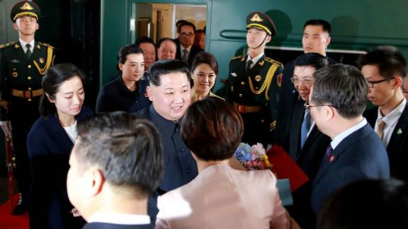 Kim Jong Un, center, and his wife, Ri Sol Ju, center right, are greeted by Chinese officials in Beijing.