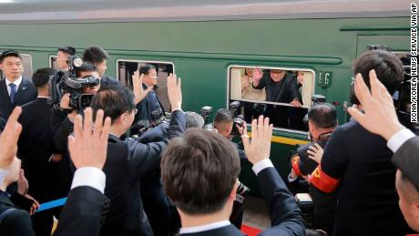 Kim Jong Un waves during his sendoff from Beijing station Tuesday.