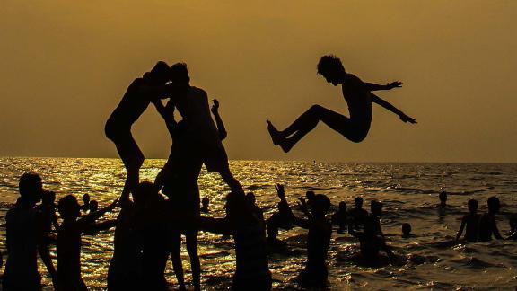 Mumbai, India: A group of tourists forms a human pyramid at sunset on Mumbai