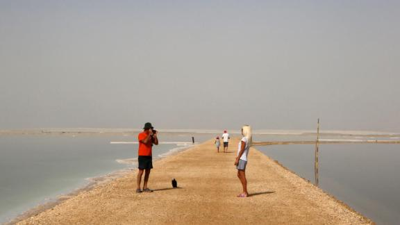 Neve Zohar, Israel: Tourists pose for pictures on an embankment between evaporation ponds -- used to remove salt from the water -- in the southern part of the Dead Sea in community settlement Neve Zohar.