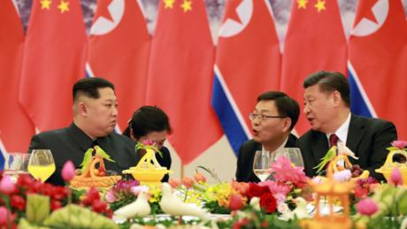 Kim Jong Un, left, and Xi Jinping, right, are seen at a banquet in this photo released by North Korean state media.