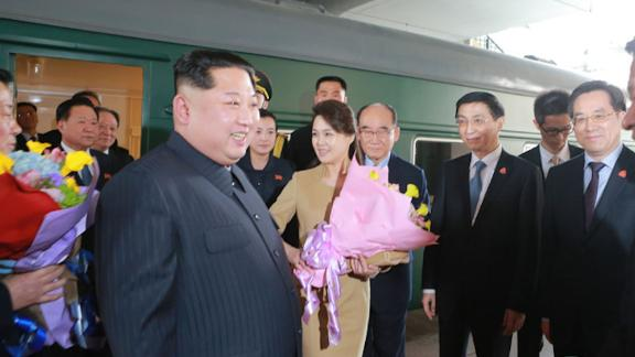 Kim Jong Un and his wife Ri Sol Ju are seen outside what appears to be the Kim