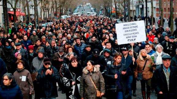 Participants walk holding placards during a silent march in Paris on March 28, 2018, in memory of Mireille Knoll, an 85-year-old Jewish woman murdered in her home in what police believe was an anti-Semitic attack. The partly burned body of Mireille Knoll, who escaped the mass deportation of Jews from Paris during World War II, was found in her small apartment in the east of the city on March 23, by firefighters called to extinguish a blaze. / AFP PHOTO / FRANCOIS GUILLOT        (Photo credit should read FRANCOIS GUILLOT/AFP/Getty Images)