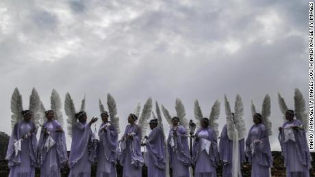 OURO PRETO, BRAZIL - APRIL 05:  Women dressed as angels gather to pose for a group photo before the annual Easter procession during traditional Semana Santa (Holy Week) festivities on April 5, 2015 in Ouro Preto, Brazil. Holy Week marks Easter celebrations for Catholics and Brazil holds the largest number of Catholics on the planet. Ouro Preto was a colonial mining town founded in the late 17th century and the Semana Santa tradition in Ouro Preto can be traced back to the 18th century Portuguese colonial period.  (Photo by Mario Tama/Getty Images)