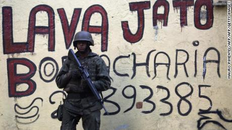 A Brazilian soldier stands guard in front of a graffiti ardvertising a car wash (Lava Jato), the name of the anticorruption operation that shook up the country, during an operation in the Rocinha favela in Rio de Janeiro, Brazil on September 26, 2017.  Security officials said the giant Rocinha favela in Rio de Janeiro was back under control Saturday after hundreds of soldiers and police were sent to battle heavily armed drug traffickers. / AFP PHOTO / Mauro PIMENTEL        (Photo credit should read MAURO PIMENTEL/AFP/Getty Images)
