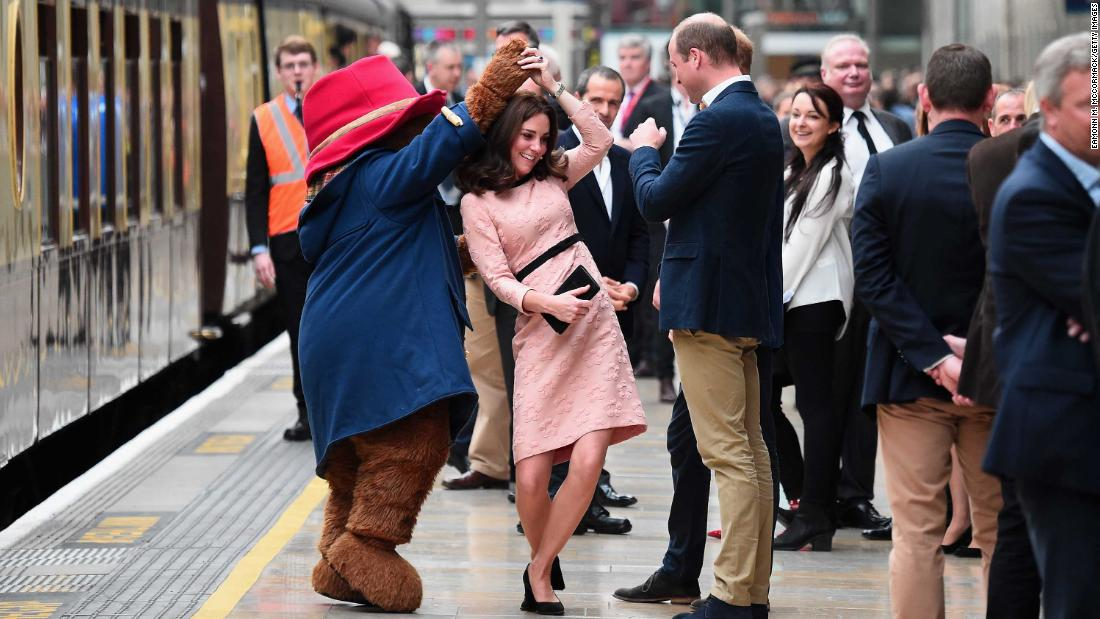Paddington Bear dances with Catherine while Prince William looks on during the Charities Forum Event at Paddington Station in London, on October 16, 2017.