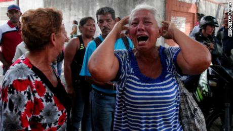 A relative of a prisoner cries in front of a police station in Valencia on March 28, 2018, after a fire engulfed police holding cells that resulted in the deaths of 68 people. A total of 68 people died on March 28 during an attempted jailbreak in Venezuela after a fire engulfed police holding cells in one of the worst tragedies in years in a notoriously violent and overcrowded prison system. / AFP PHOTO / Katherine ORTIZ / The erroneous mention[s] appearing in the metadata of this photo by Katherine ORTIZ has been modified in AFP systems in the following manner: [2018] instead of [2017]. Please immediately remove the erroneous mention[s] from all your online services and delete it (them) from your servers. If you have been authorized by AFP to distribute it (them) to third parties, please ensure that the same actions are carried out by them. Failure to promptly comply with these instructions will entail liability on your part for any continued or post notification usage. Therefore we thank you very much for all your attention and prompt action. We are sorry for the inconvenience this notification may cause and remain at your disposal for any further information you may require. (Photo credit should read KATHERINE ORTIZ/AFP/Getty Images)