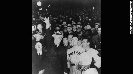 President Franklin Delano Roosevelt (1882 - 1945) throws the ball into play at a baseball game.