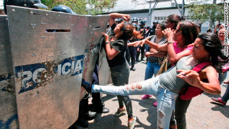 A woman kicks at a riot police shield as relatives of prisoners wait to hear news about their family members imprisoned at a police station where a riot broke out, in Valencia, Venezuela, Wednesday, March 28, 2018. In a state police station housing more than one hundred prisoners, a riot culminated in a fire, requiring authorities to open a hole in a wall to rescue the inmates. (AP Photo/Juan Carlos Hernandez)
