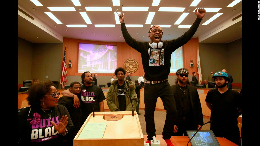 "Stevante Clark stands on a desk as he shouts the name of his brother <a href=""https://www.cnn.com/2018/03/28/us/stephon-clark-brother-trnd/index.html"" target=""_blank"">at a City Council meeting</a> in Sacramento, California, on Tuesday, March 27. Stephon Clark, 22, was fatally shot by police earlier this month. Officers had pursued him over a call about a man breaking car windows, and he was shot in his grandmother's yard after a brief encounter lasting less than a minute, police said. The officers said they thought he had a gun, but only his cell phone was found on the scene. His death has triggered protests in the city."
