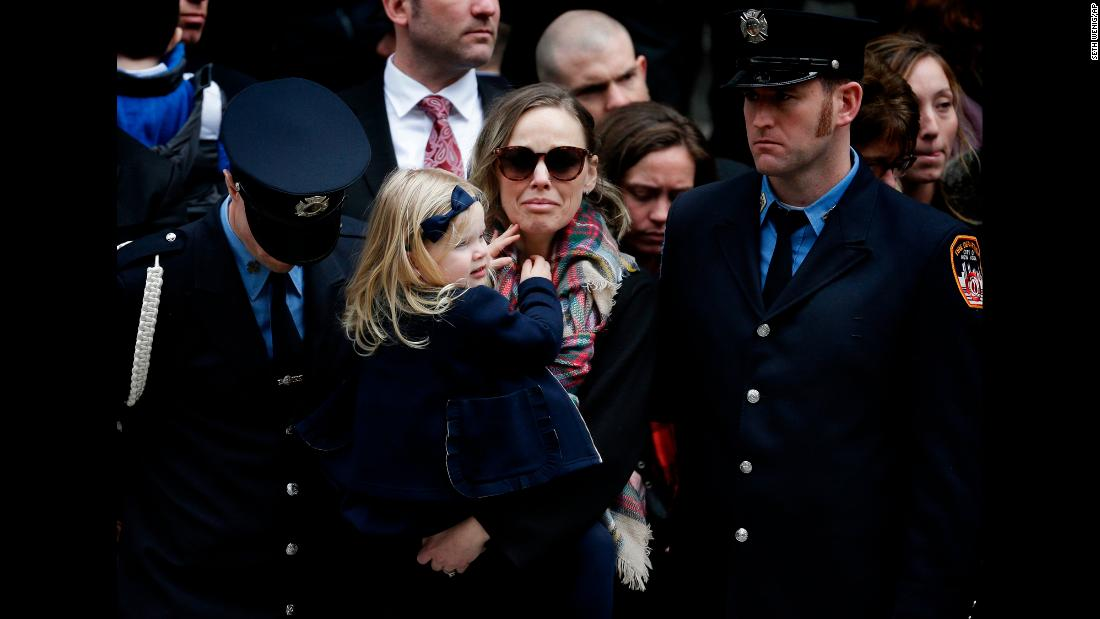 "Eileen Davidson holds her daughter Emily during her husband's funeral in New York on Tuesday, March 27. Michael Davidson, 37, <a href=""https://www.cnn.com/2018/03/23/us/firefighters-killed-new-york-pennsylvania/index.html"" target=""_blank"">died while fighting a five-alarm fire on a movie set.</a>"