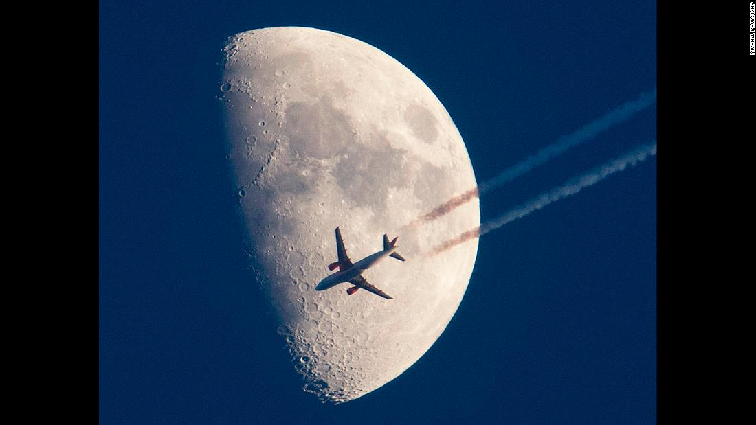 An airplane is photographed in front of the moon as it flies over Frankfurt, Germany, on Sunday, March 25.