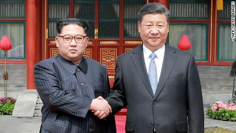 This picture from North Korea's official Korean Central News Agency (KCNA) taken on March 27, 2018 and released on March 28, 2018 shows China's President Xi Jinping (R) shaking hands with North Korean leader Kim Jong Un in Beijing.