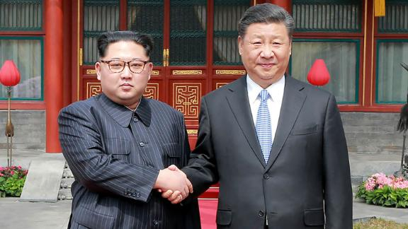 A photograph from North Korea's official Korean Central News Agency (KCNA) released on March 28, 2018 shows China's President Xi Jinping (right) shaking hands with North Korean leader Kim Jong Un in Beijing.