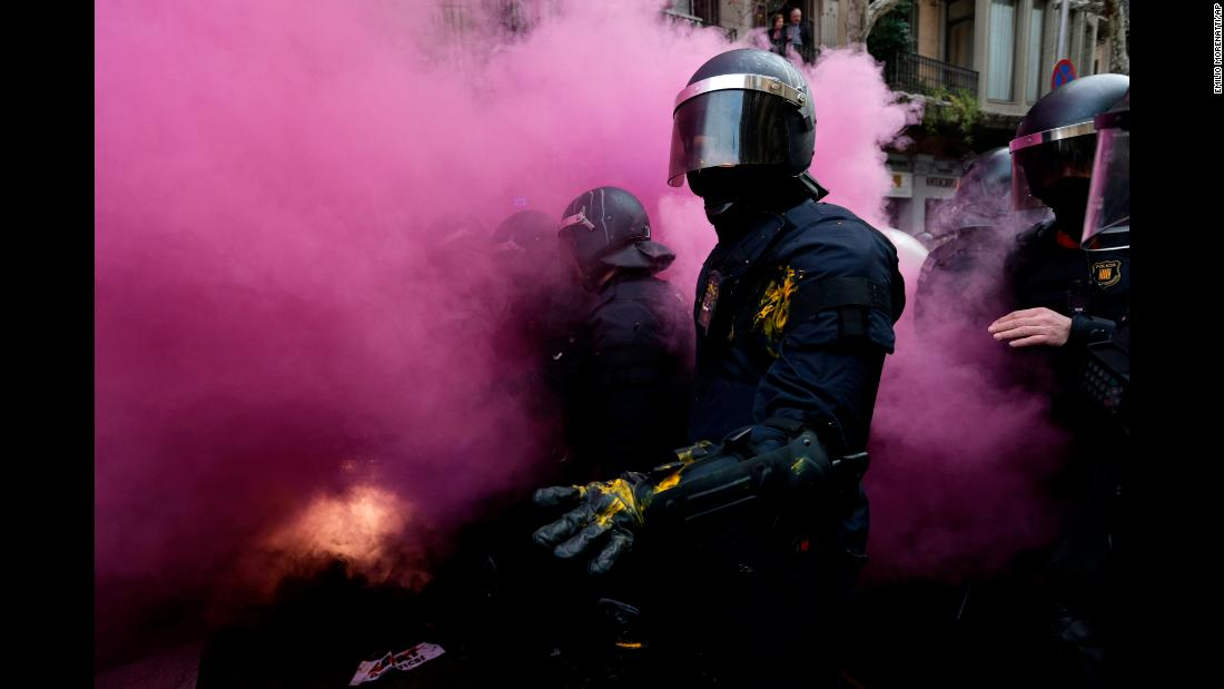 "Regional police officers stand amid smoke from a smoke bomb during protests in Barcelona, Spain, on Sunday, March 25. <a href=""https://www.cnn.com/2018/03/25/europe/carles-puigdemont-detained-germany/index.html"" target=""_blank"">Protests broke out</a> after news spread that Catalonia's former separatist leader, Carles Puigdemont, had been detained in Germany. Puigdemont had been living in self-imposed exile after spearheading Catalonia's referendum on whether to secede from Spain."